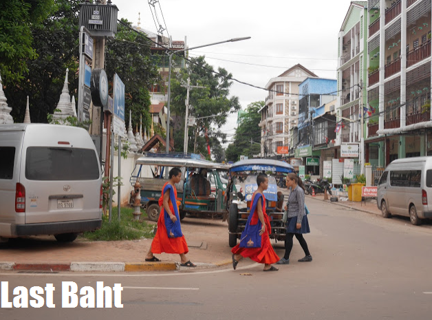 monks in saffron robes cross the street in Vientiane, Laos