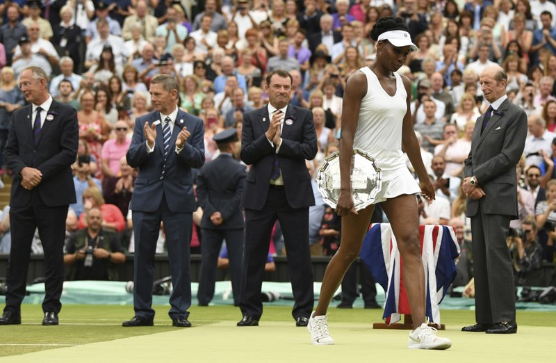 Venus Williams of the United States holds the runners-up plate after losing to Spain's Garbine Muguruza in the Women's Singles final match on day twelve at the Wimbledon Tennis Championships in London Saturday, July 15, 2017 David Ramos/Pool Photo via AP