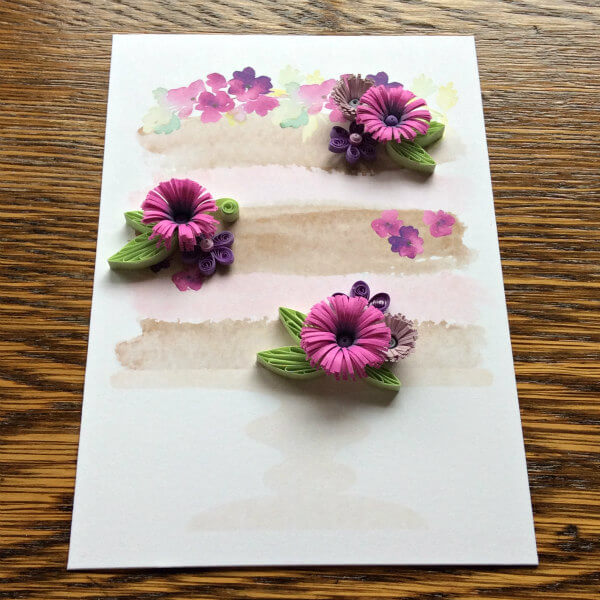 quilled flower motif on a watercolor wedding cake card