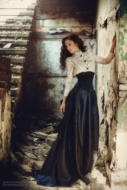 Women's Steampunk, Victoriana or Neo-Victorian fashion. This elegant neo-victorian outfit consists of clothing like white high collar victorian style blouse, black underbust corset, long black satin bell skirt.