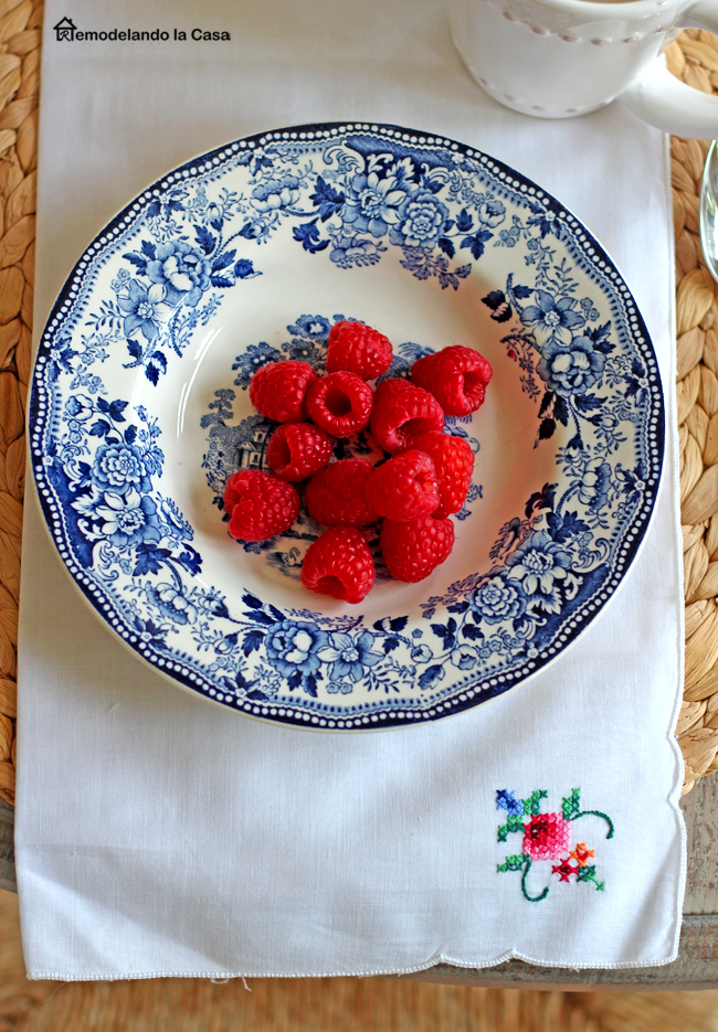 white and blue plates with raspberries and napkin with crossed stitched design