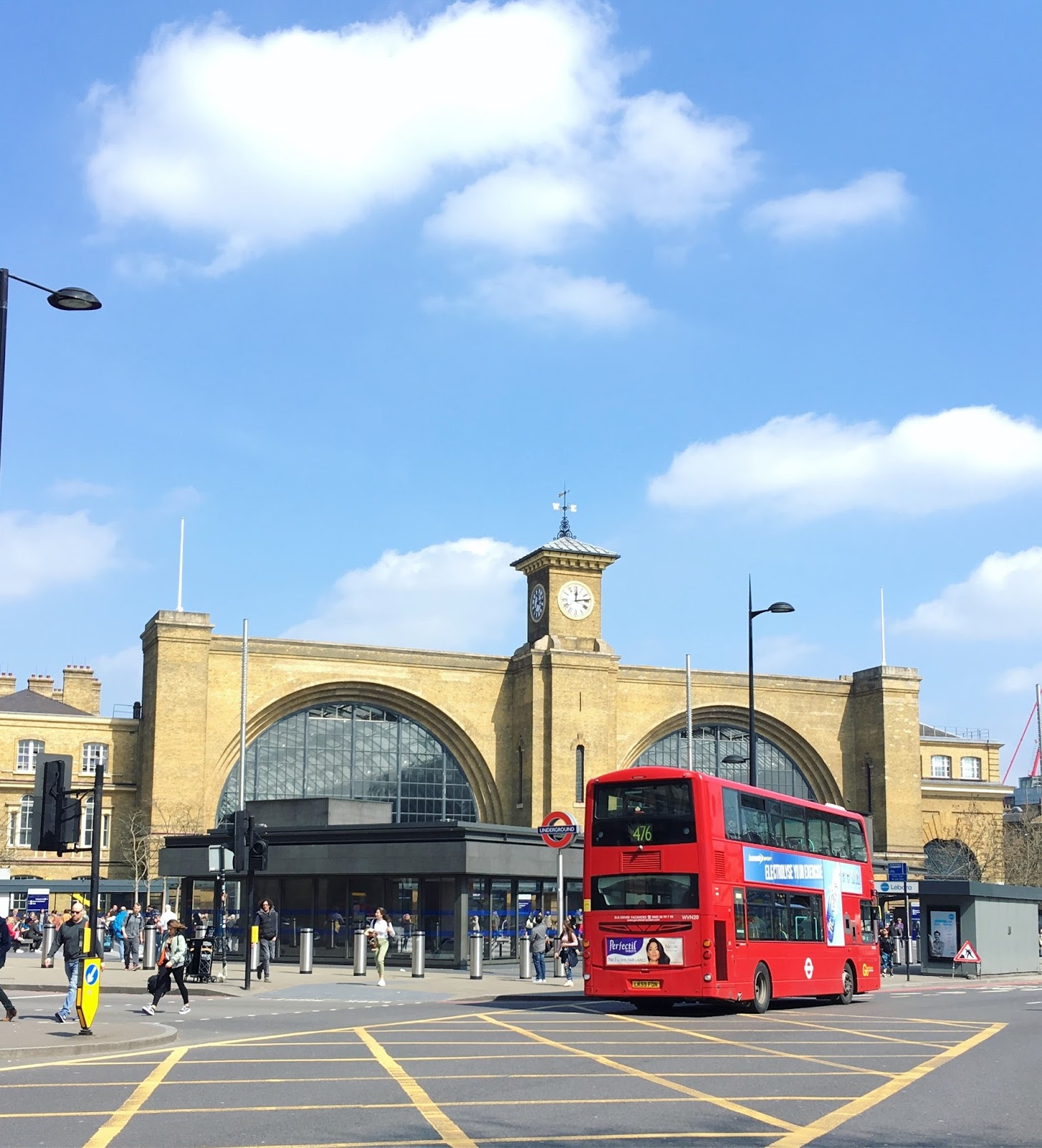 Kings Cross station can be seen, the sky is blue and a red double decker bus is visible.