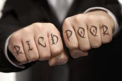 Rich VS Poor written on hand knuckles