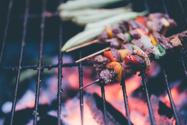 A lit barbecue with skewer kebabs on the rack