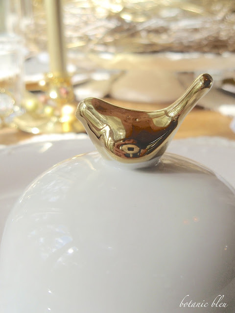Thanksgiving gold and white table setting with gold bird topped white cloche