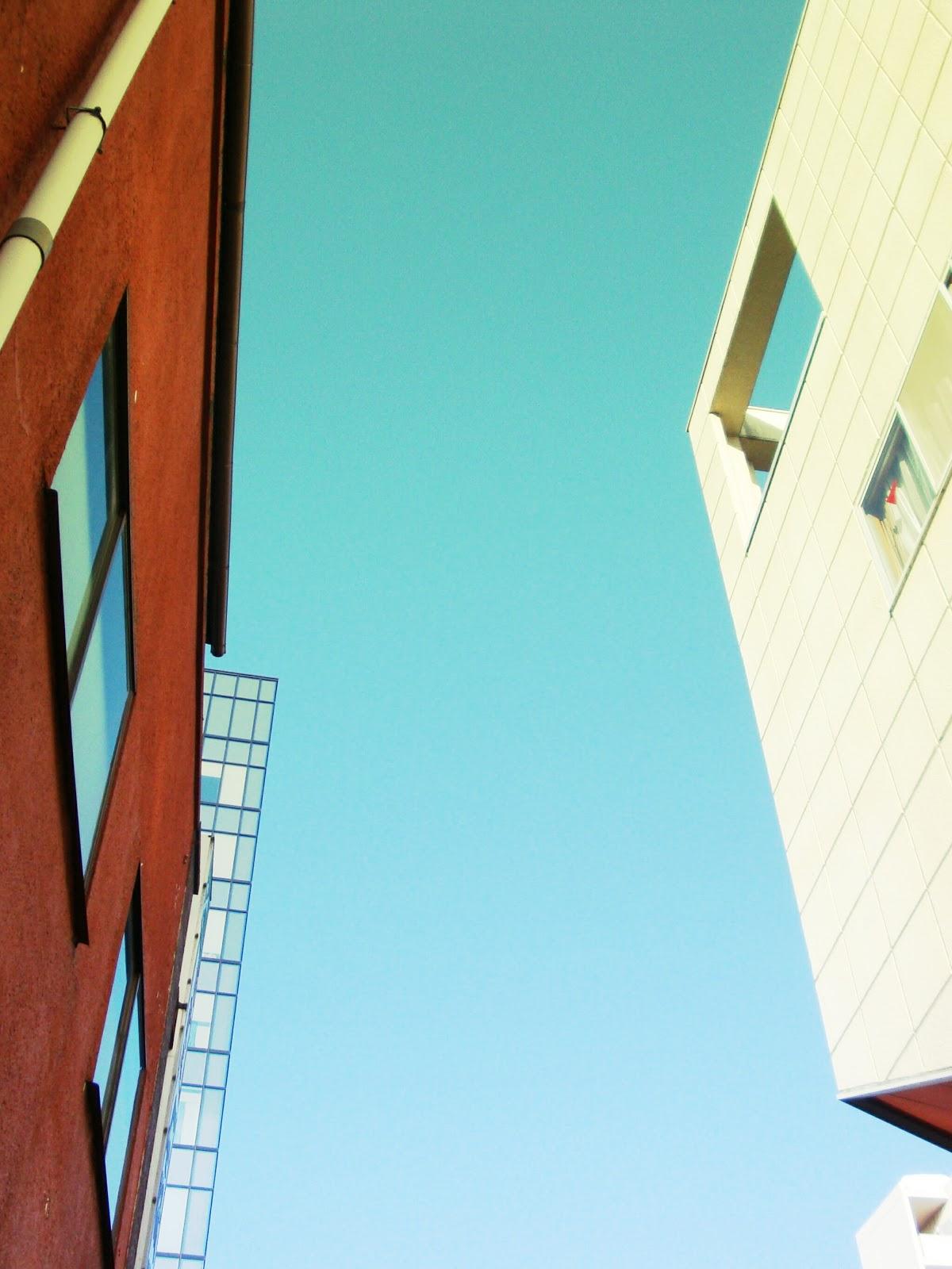 茶色と薄黄色の建物の間から青空が覗いている