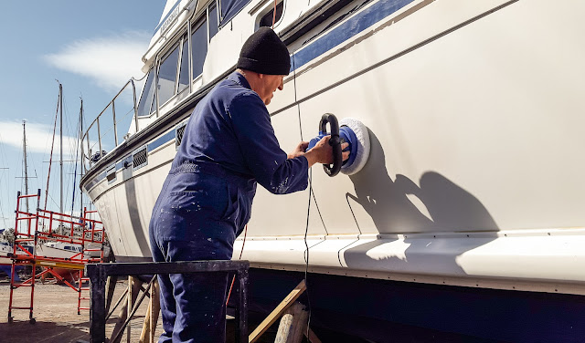 Photo of Phil applying rubbing compound to the port side of Ravensdale's hull