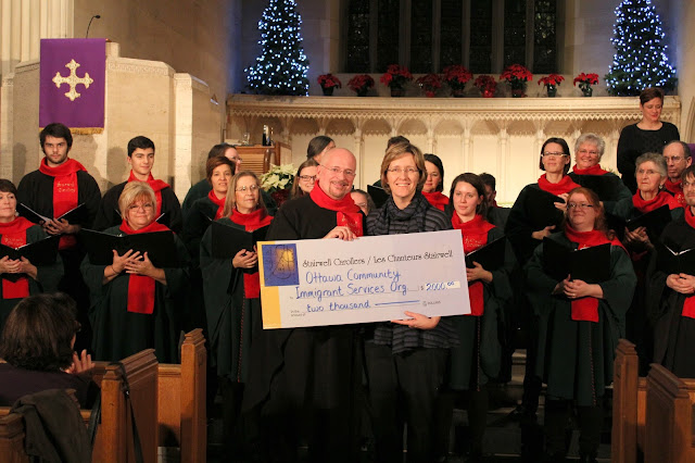 The Stairwell Carollers present a charitable gift to Immigrant services, 2015 concert