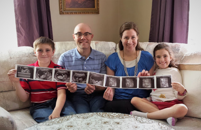 The Lundy Family holding ultrasound pictures of Baby Stafford!