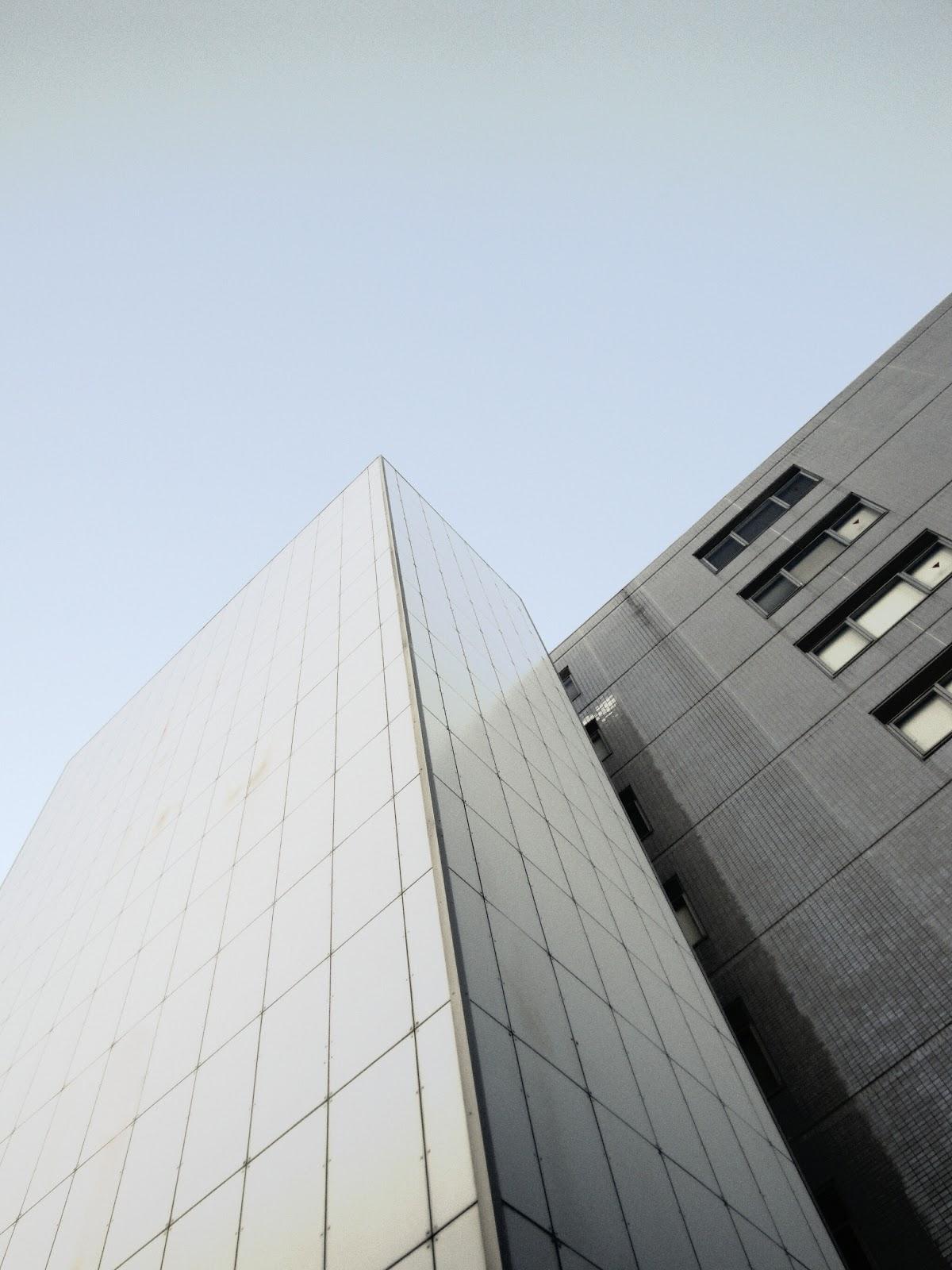 薄茶と白のビルが空に向かって並ぴ建っている
