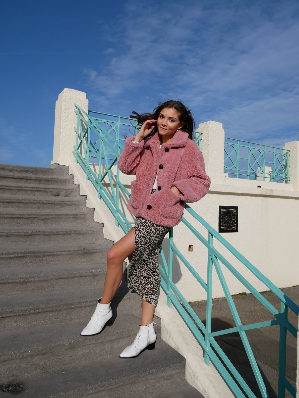 Style blogger in pink coat, leopard print skirt, white boots outside retro building