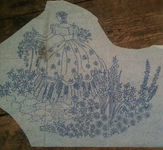 A detailed embroidery transfer for a crinoline lady in a garden.