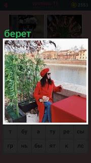 за столом сидит женщина в красном пальто и берете