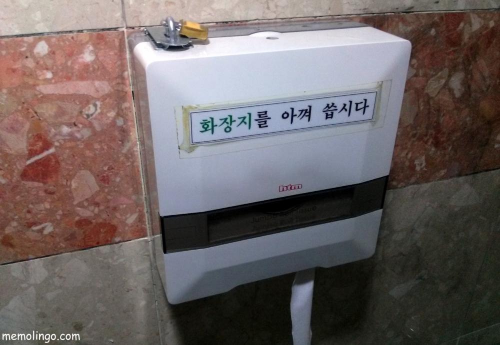 Aviso en coreano en un rollo de papel higiénico en un servicio público