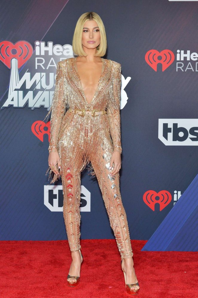 Hailey Baldwin wears sheer gold jumpsuit to the 2018 iHeart Radio Music Awards