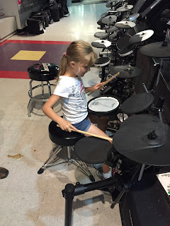 young girl learning to play drums