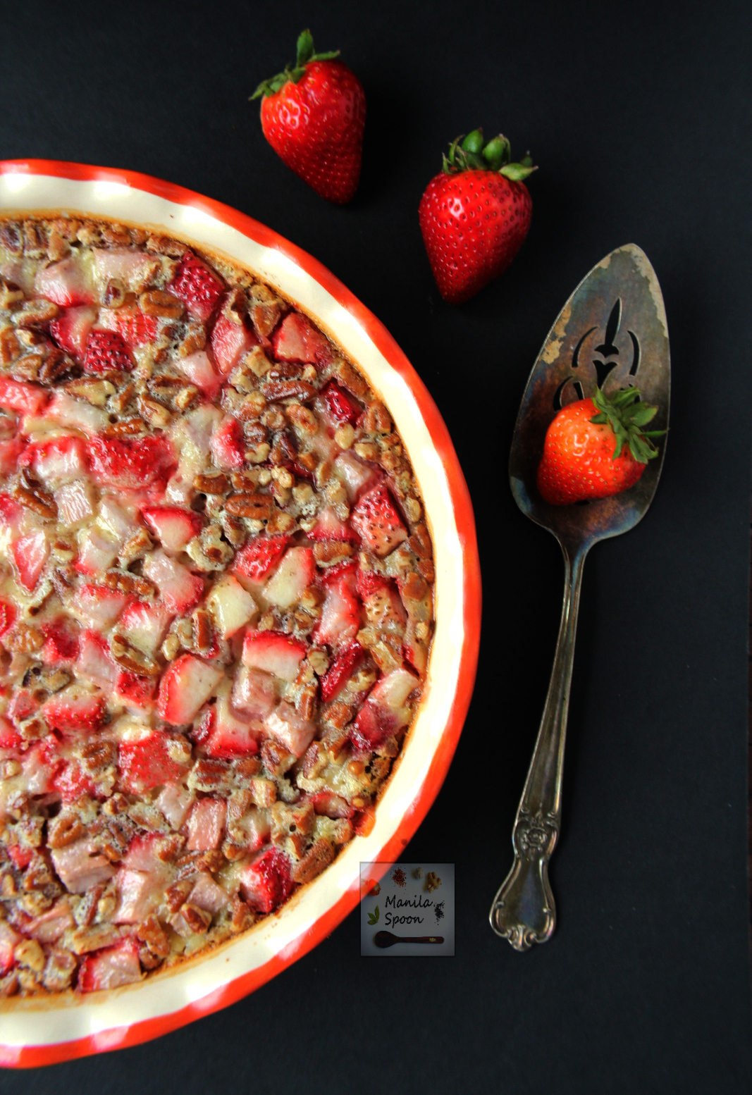 This delicious tart is unbelievably easy to make! Studded with the juiciest strawberries and crunchy pecans and then baked in a sweet vanilla custard batter it's the perfect summer dessert - Strawberry and Pecan Clafoutis | manilaspoon.com