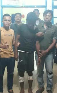 Tersangka pelaku pembunuhan (tengah) diapit polisi.