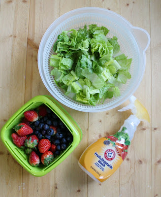 lettuce in a salad spinner and berries in a berry box getting washed with arm & hammer fruit & vegetable wash