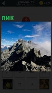 Изображение пика одной из вершин в горах под самым небом в облаках