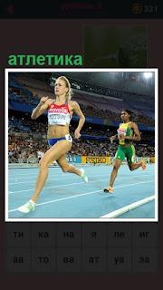 по дорожке бежит женщина с номером, занятие атлетикой