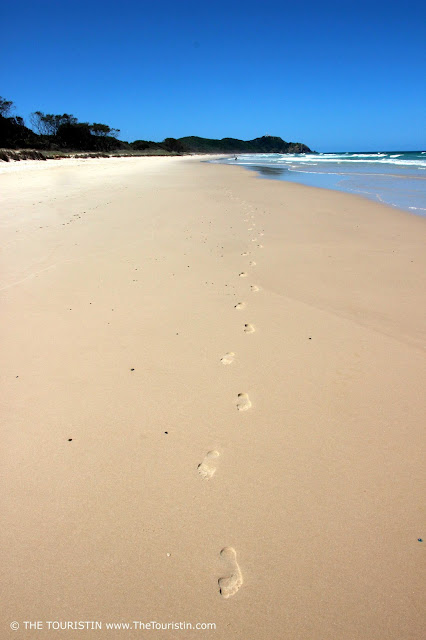 Footsteps on the beach with green hills and the ocean in the background under a cloudless blue sky..