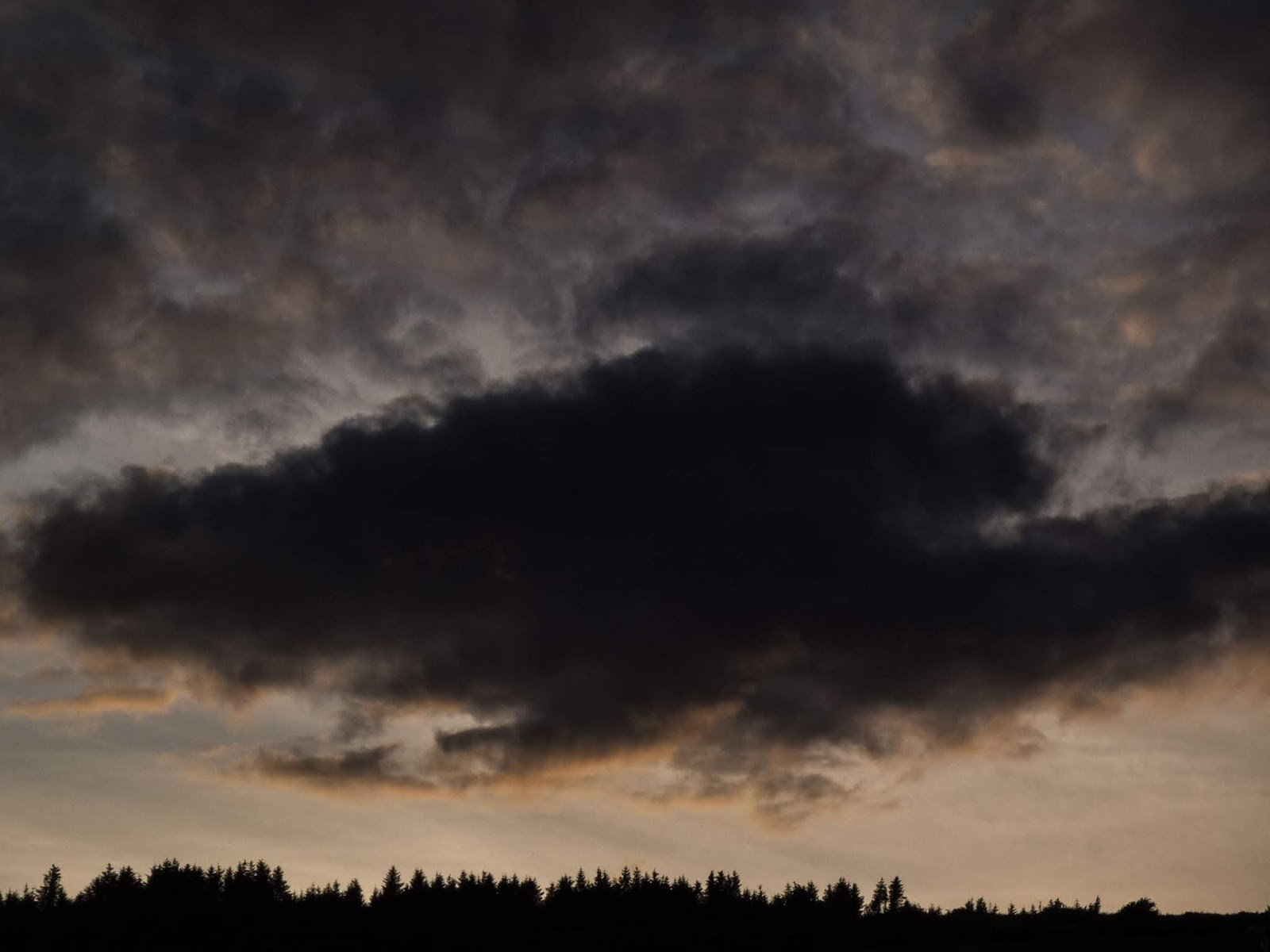 A grey toned sunset cloud over a hillside in North County Cork.