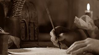 Γράφοντας με πένα υπό το φως κεριού.
