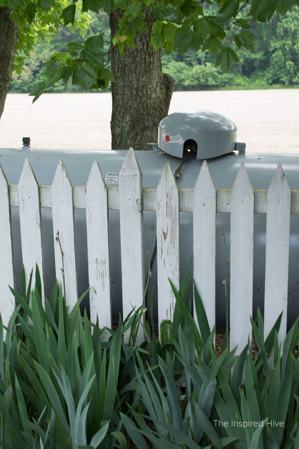 Great idea to hide a propane gas tank in the yard with a cute picket fence! Plus how to maintain the fence to keep it nice and bright.