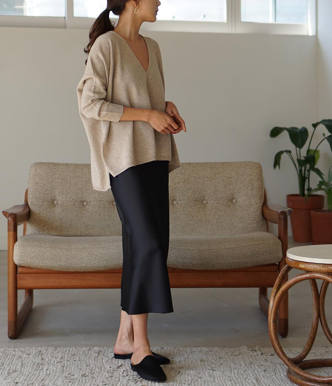 Comfy Yet Stylish Work-From-Home Outfit Idea — neutral v-neck sweater, silk black midi skirt, and black mule flats.