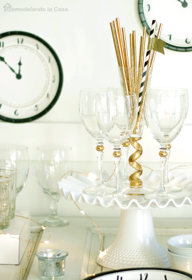 Fancy glassware on plate stand with gold paper straws