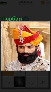 На голове у мужчины с бородой одет тюрбан цветной с украшением