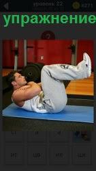 В спортивном зале на коврике спортсмен выполняет упражнение в положении лежа
