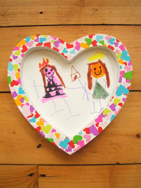 cute childs drawing showing two smiling girls in a multi coloured heart frame