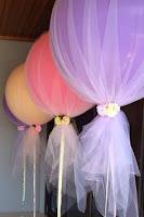 Baloane colorate invelite in tull si legate cu flori pentru decor botez