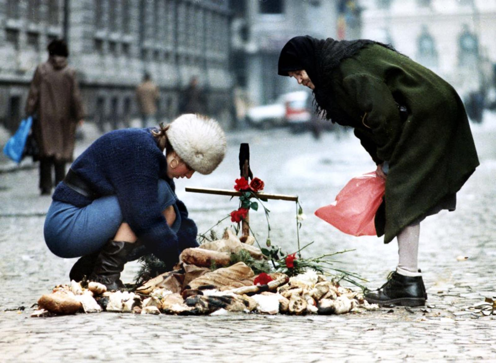 A student tends a small shrine in the middle of the main street outside Bucharest university watched by an old woman.