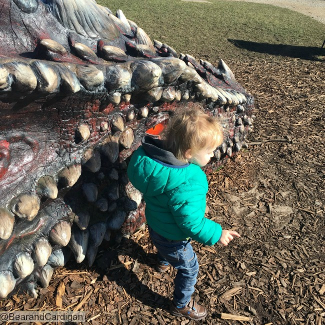 toddler next to dragons head