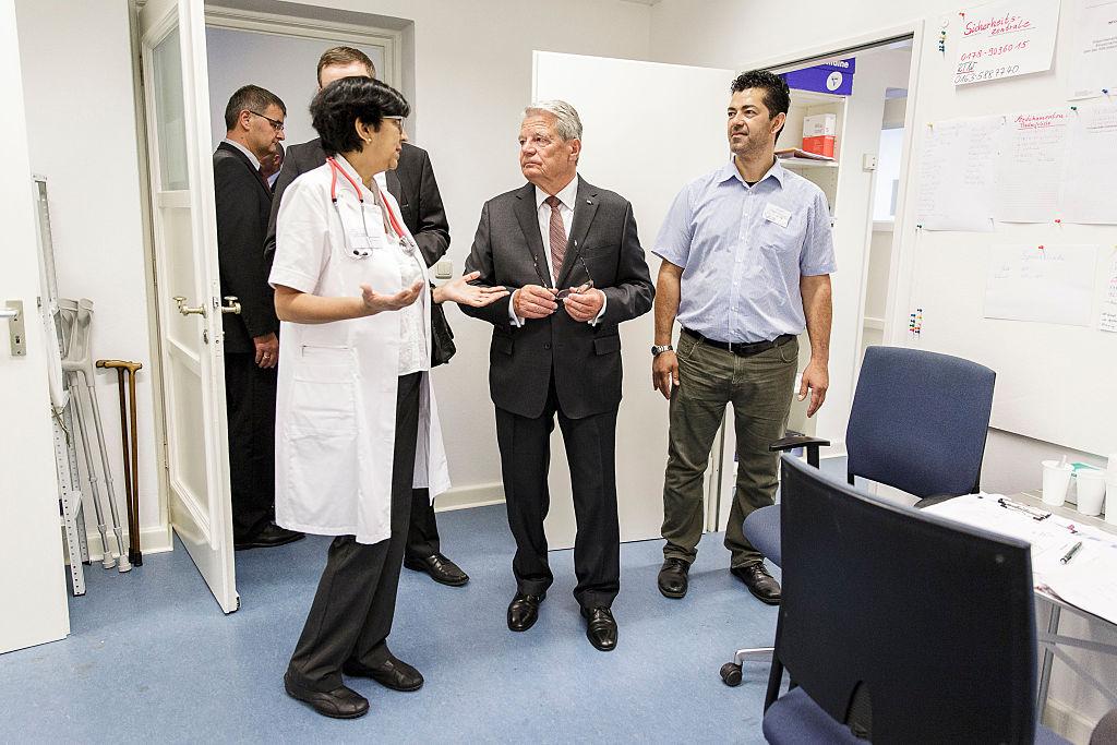Le 26 août 2015, Joachim Gauck, alors président de l'Allemagne, parle avec les médecins de l'infirmerie d'un centre d'accueil pour migrants à Berlin-Wilmersdorf, en Allemagne. (Photo de Jesco Denzel / Bundesregierung via Getty Images)
