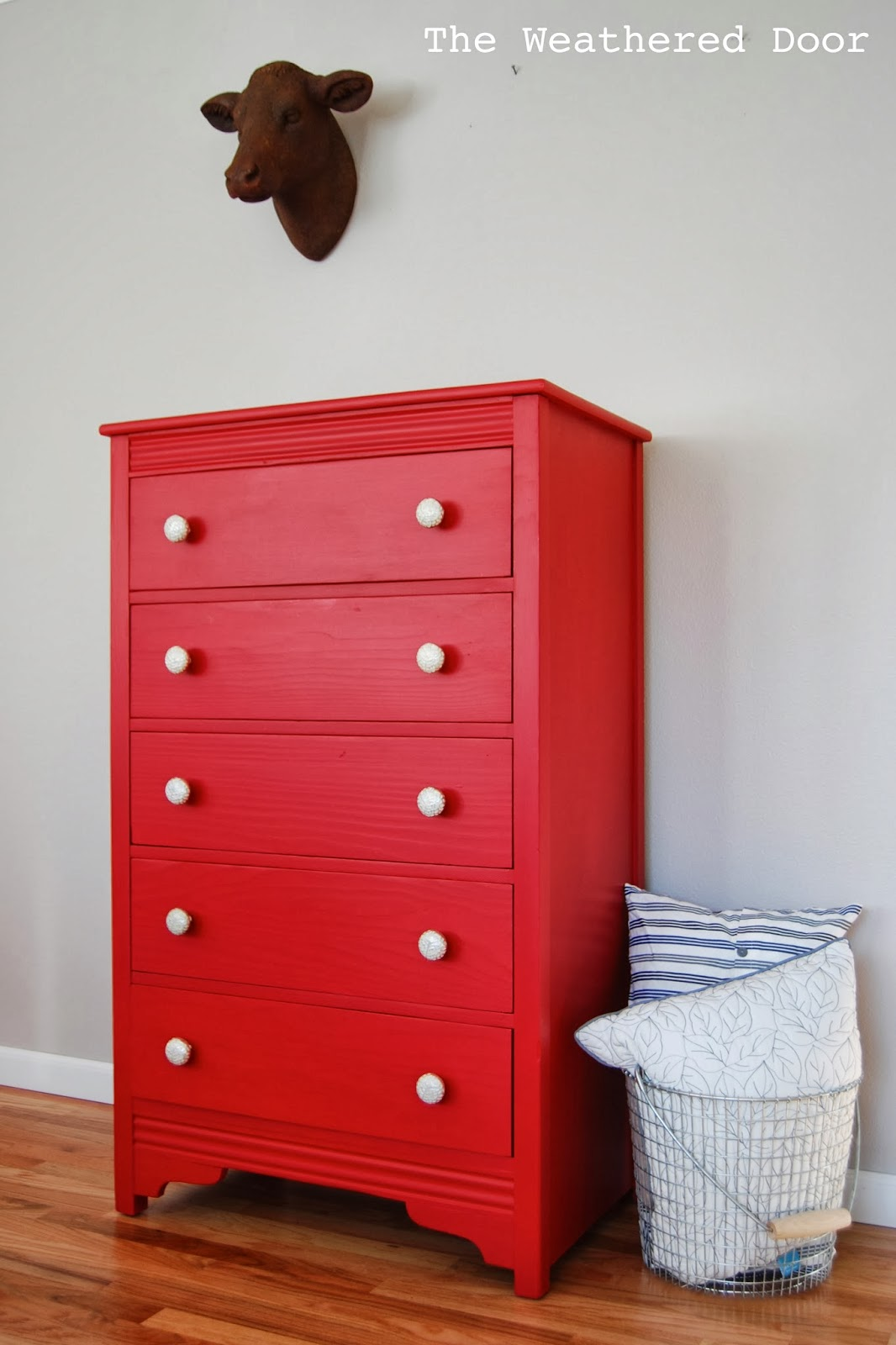 A tall red dresser with silver and white knobs  The Weathered Door