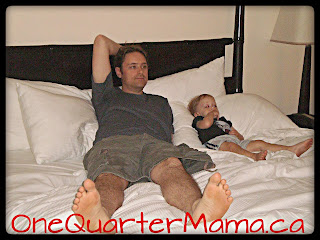 Dada and Little Man lying on hotel room bed on www.onequartermama.ca