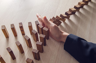 Man Stopping Dominoes From Falling