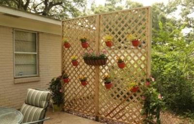 Tirai bambu atau kayu yang dihias dengan pot-pot bunga yang cantik. Menjadi sekat yang cantik untuk menciptakan privasi di halaman rumah.