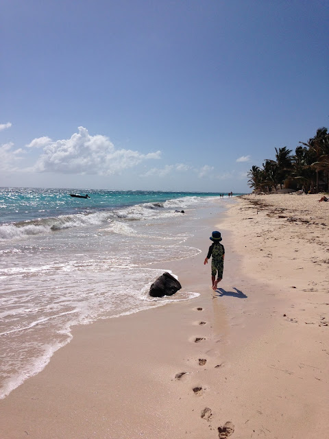 A little boy running down a deserted sand beach in San Andres, Colombia.