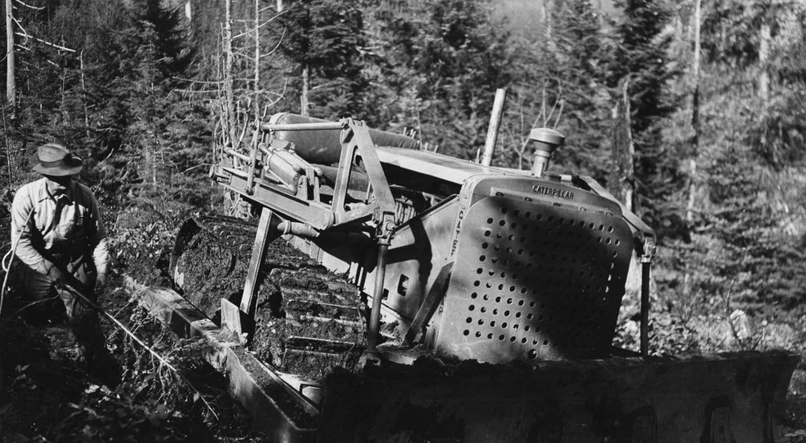 A logger uses a bulldozer to build a road through the forest. 1930.