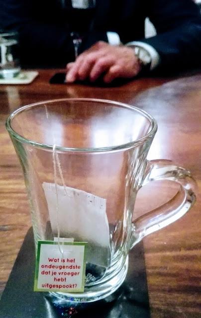Kleurenfoto van een glas op tafel met label van theezakje met de tekst: Wat is het ondeugendste dat je vroeger hebt uitgespookt. Tegenover zit een heer in het zwart met een glas rode wijn en een glas water.