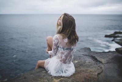 Chica rubia sentada en una roca con el mar delante