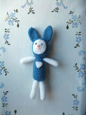 Bordered by a cross stitch floral pattern, this amigurumi bunny has a blue body, head and ears with white arms and legs.  The white face is appliqued with embroidered features - black eyes and pink nose and mouth. A white appliqued love heart features on the chest.