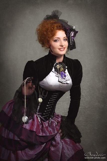 Woman dressed in steampunk clothing (purple tiered skirt, ruffle blouse and velvet jacket, hat, gloves) - Female steampunk fashion and costumes