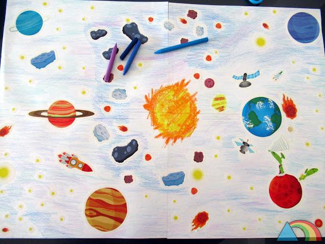 Mural del Sistema Solar hecho con pegatinas de los planetas y ceras de colores
