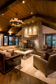 Fabulous View of the Family Room with Wide Rustic Fireplace Mantels and Brown Sofas on Brown Carpet